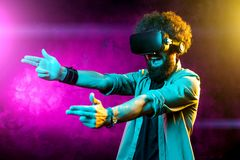 Photo of handsome bearded hipster man with curly hair shooting virtual guns with goggles in neon lights. Smartphone. Using with VR headset royalty free stock photos