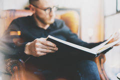 Photo handsome bearded scientist wearing glasses black shirt.Man sitting in vintage chair university library, reading book and rel. Axing. Blurred background Stock Photo
