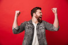 Photo of handsome cheerful man 30s in jeans jacket screaming and stock photography