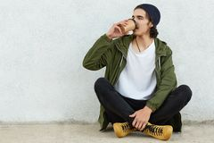 Photo of handsome curly teenager in stylish outfit, enjoys fresh coffee, sits in lotus pose crossed legs against white concrete wa stock photography