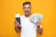 Emotional man posing isolated over yellow wall background holding passport with tickets and money royalty free stock image