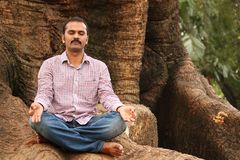 Photo of a handsome indian executive meditating Royalty Free Stock Photo