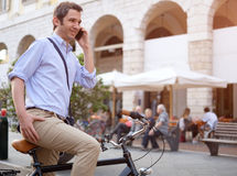 Photo of a handsome man holding smartphone in city Stock Images