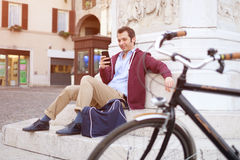 Photo of a handsome man holding smartphone in city Royalty Free Stock Photos