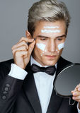 Photo of handsome man tweezing the hair on his face. Stock Image