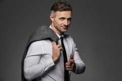Photo of handsome man wearing business suit pointing finger on c. Amera and holding jacket over his shoulder isolated over gray background Royalty Free Stock Image