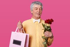 Photo of handsome mature man with grey hair, wears elegant yellow shirt, bowtie, holds bouquet of red roses and pink bag with royalty free stock photos