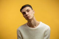 Portrait of a smart serious young man standing against yellow background. Photo of handsome serious thin man wearing white jersey, looks confidently into camera stock photo