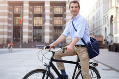 Photo of a handsome smiling man riding bike in city. Picture of a young smiling business man on a bicycle on his way home from work while the sun is setting. He Stock Images