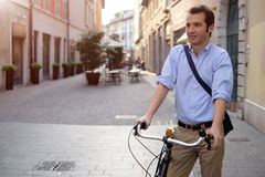 Photo of a handsome smiling man riding bike in city. Picture of a young smiling business man on a bicycle on his way home from work while the sun is setting. He Royalty Free Stock Image