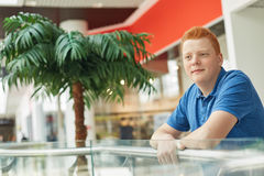 A photo of handsome stylish guy with trendy haircut and red hair dressed in casual blue T-shirt posing in a mall against big green Royalty Free Stock Photography