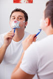 Photo of handsome young man shaving and looking at himself in th Stock Photo
