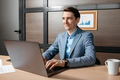 Photo of handsome young manager working with laptop and business documents in modern office. royalty free stock photo