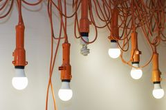 Photo of hanging light bulbs with depth of field. One light does not Shine. Leadership concept. stock photography