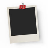 The photo hanging on an office paper clip. On a white background Royalty Free Stock Images