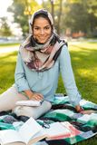 Photo of happy arabian woman wearing headscarf reading books royalty free stock images