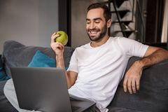 Photo of happy bachelor using silver laptop while sitting on couch in living room. Photo of happy bachelor 30s wearing casual t-shirt using silver laptop while stock images
