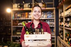 Photo of happy brunette seller with wooden box with wine in store. On background of shelves stock images