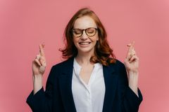 Photo of happy businesswoman crosses fingers for good luck, believes everything will be fine, prays over pink background, has royalty free stock photos