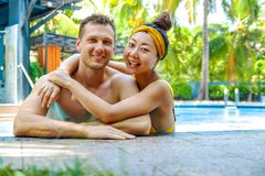 Beautiful photo of happy couple in the pool chatting with each other. stock images
