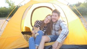 Young Happy couple with cat sitting in tent during hiking trip stock video footage
