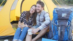 Young happy couple with cat sitting in tent during hiking trip stock video