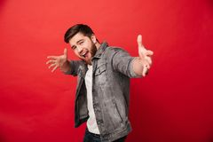 Photo of happy ecstatic guy 30s wearing beard in jeans jacket ha. Ving fun and posing with open hands  over red background Royalty Free Stock Images
