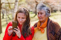Happy elderly woman with her daughter. Photo of happy elderly women with her daughter taking selfie Royalty Free Stock Images