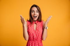 Photo of happy excited amazed young woman in red dress standing. With open palms, looking at camera, isolated on yellow background Royalty Free Stock Images