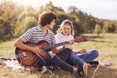 Photo of happy friends entretain themselves, sing songs and play guitar, have joyful expressions, sit on ground, dressed in casual. Clothes, enjoy summer sunny stock image