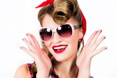 Happy girl in pin-up style wearing sunglasses on white background stock photography