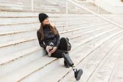 Photo of happy handicapped woman in black sportswear with prosthetic leg sitting at the street stairs, and holding thermos cup. Photo of happy handicapped woman stock photography