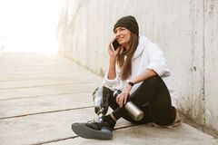 Photo of happy handicapped woman in casual wear having bionic le. G sitting on concrete floor outside and talking on mobile phone royalty free stock photos