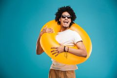 Handsome young african curly man holding rubber ring. royalty free stock photography