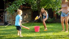 Photo of happy laughing family splashing water with water guns and garden hose at backyard. People playing and having. Image of happy laughing family splashing royalty free stock photo