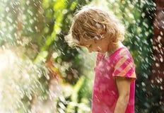 Photo of happy little girl standing under summer rain Stock Photos