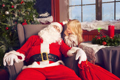Photo of happy littlle smiling girl looking at sleeping Santa Cl Stock Photos