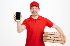 Photo of happy man from delivery service in red t-shirt and cap. Holding stack of pizza boxes and showing smartphone  over white background Stock Photos