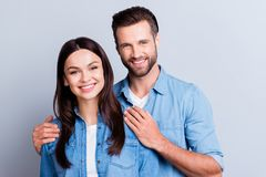 Photo of happy married couple, husband holding his hands on his. Wife`s shoulders against gray background royalty free stock photography