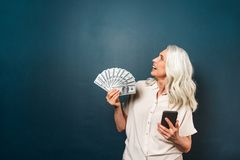 Happy mature old woman holding money in hands. Photo of happy mature old woman isolated over dark blue background. Looking aside holding money in hands using Stock Photos