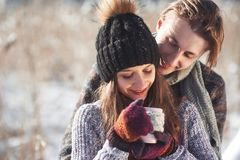 Photo of happy man and pretty woman with cups outdoor in winter. Winter holiday and vacation. Christmas couple of happy stock photos
