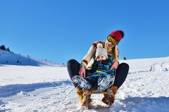 Photo of happy mother and child playing in the snow with a sledge in a sunny winter day Stock Images