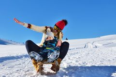 Photo of happy mother and child playing in the snow with a sledge in a sunny winter day Royalty Free Stock Photography