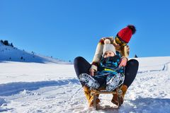 Photo of happy mother and child playing in the snow with a sledge in a sunny winter day Stock Image