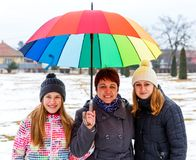 Happy mother and daughters. Photo of happy mother and daughters under colorful umbrella Royalty Free Stock Photos