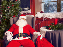 Photo of happy Santa Claus with big bag of presents sleeping Stock Images