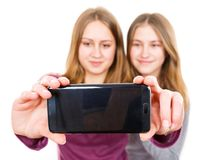 Smiling young sisters taking selfie. Photo of happy smiling young sisters taking selfie Royalty Free Stock Photography
