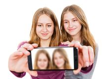 Smiling young sisters taking selfie. Photo of happy smiling young sisters taking selfie Royalty Free Stock Photos