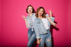 Women friends showing peace gesture. royalty free stock photos