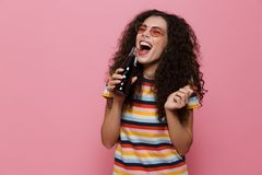 Photo of happy woman 20s with curly hair drinking soda from glass bottle, isolated over pink background. Photo of happy woman 20s with curly hair drinking soda royalty free stock photo